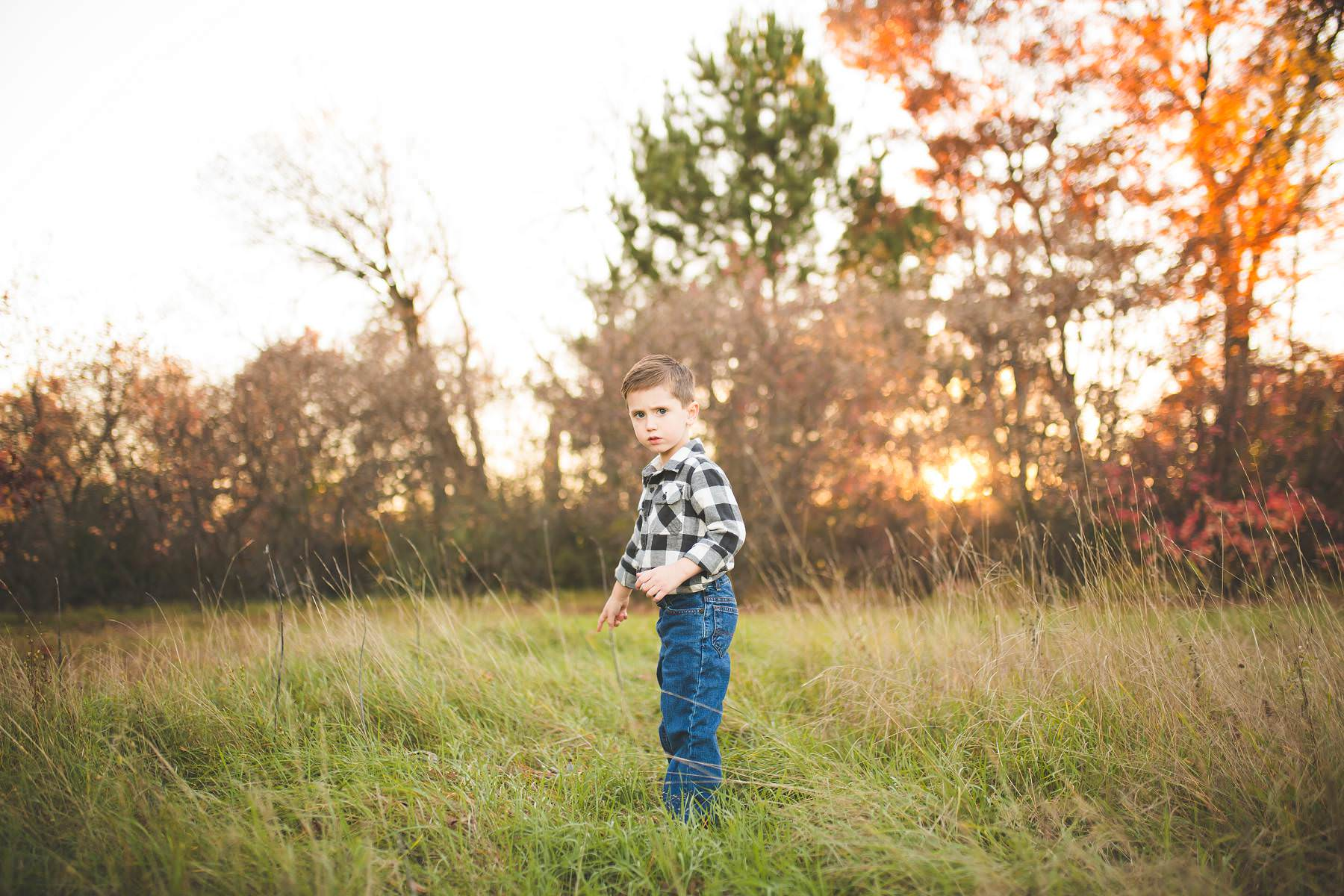 boy plays at sunset on old tree farm