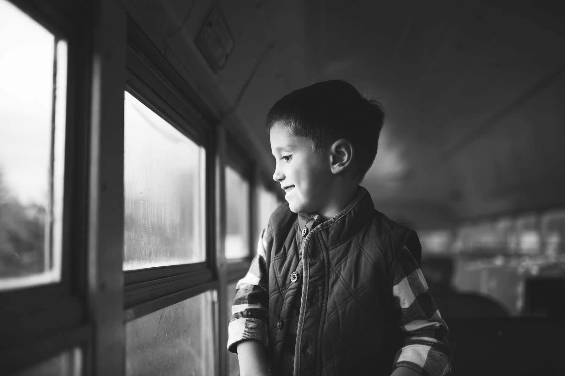 boy looks out window of antique school bus