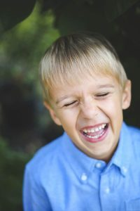 little boy in blue laughs and shows his missing tooth