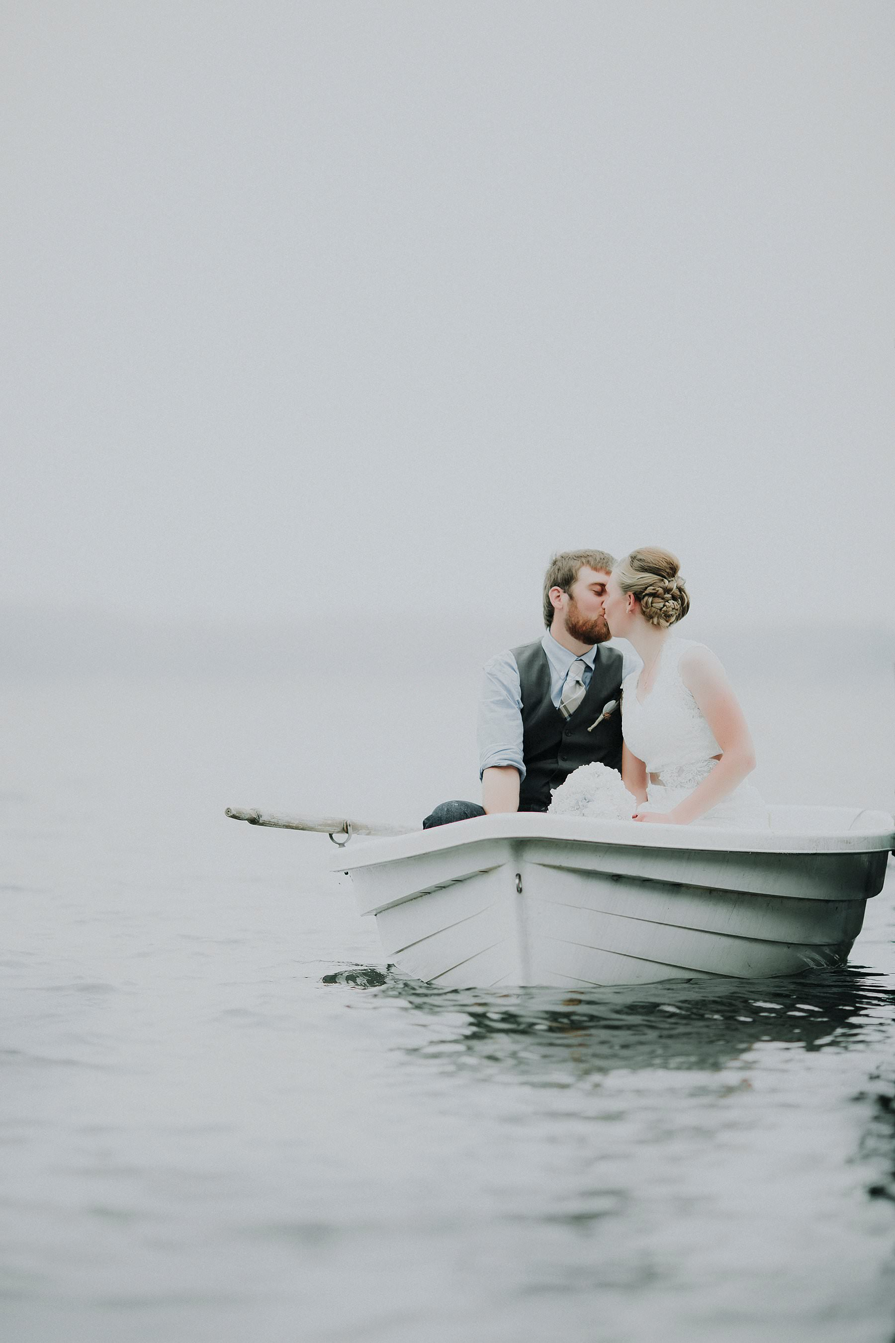 bride and groom in row boat kissing minnesota