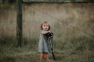 little girl in blue dress holding vintage camera