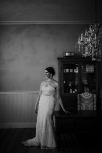 bride leaning against fancy desk in her wedding dress